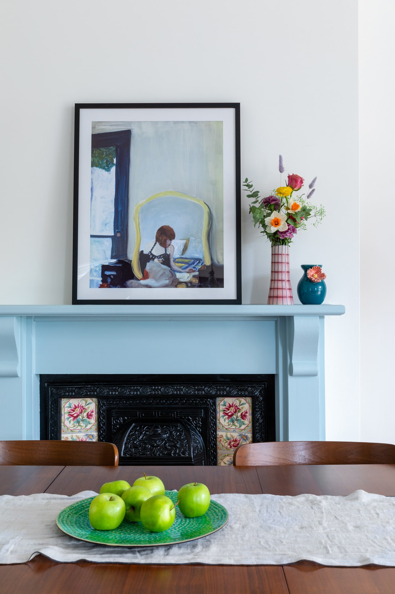 Interior detail photo of adining area: wooden table with green apples on a plate; blue fireplace with vases and art on top