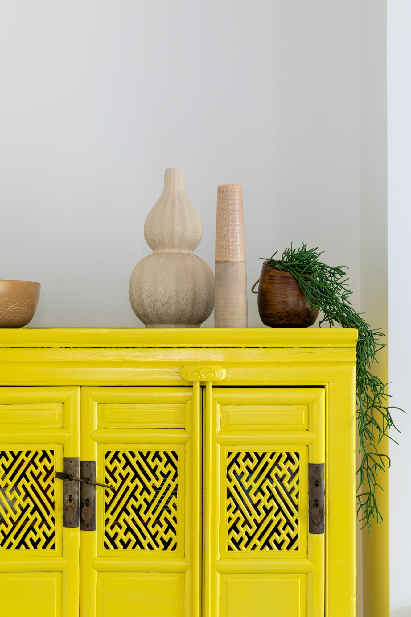 Interior photo detail: yellow cabimet with vases and plant on top