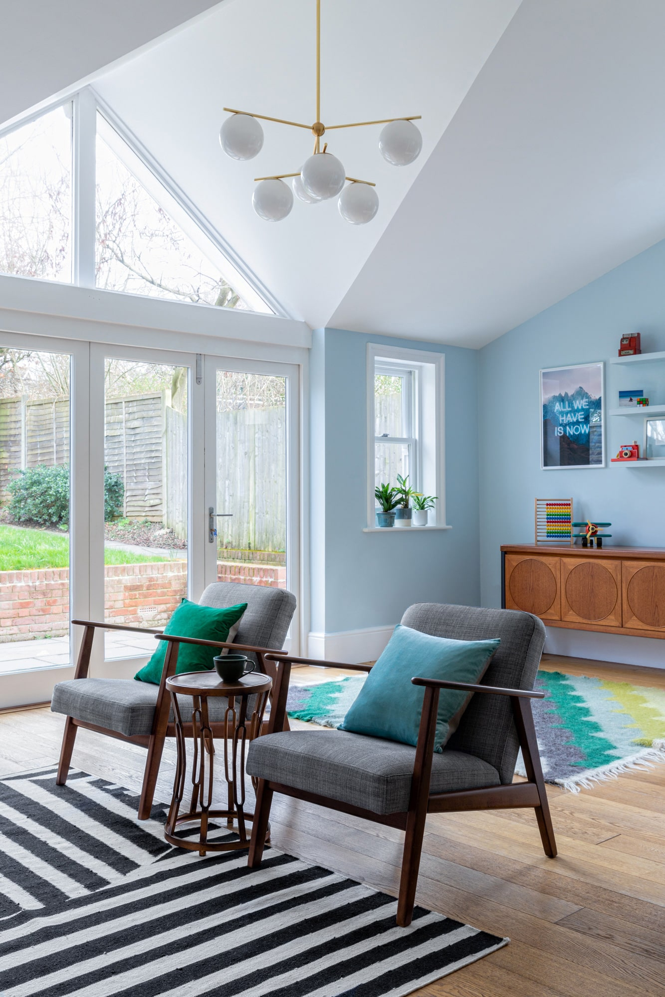 Interior photo: living room with a play area: blue walls; armchairs; wooden cabinet; colourful rug