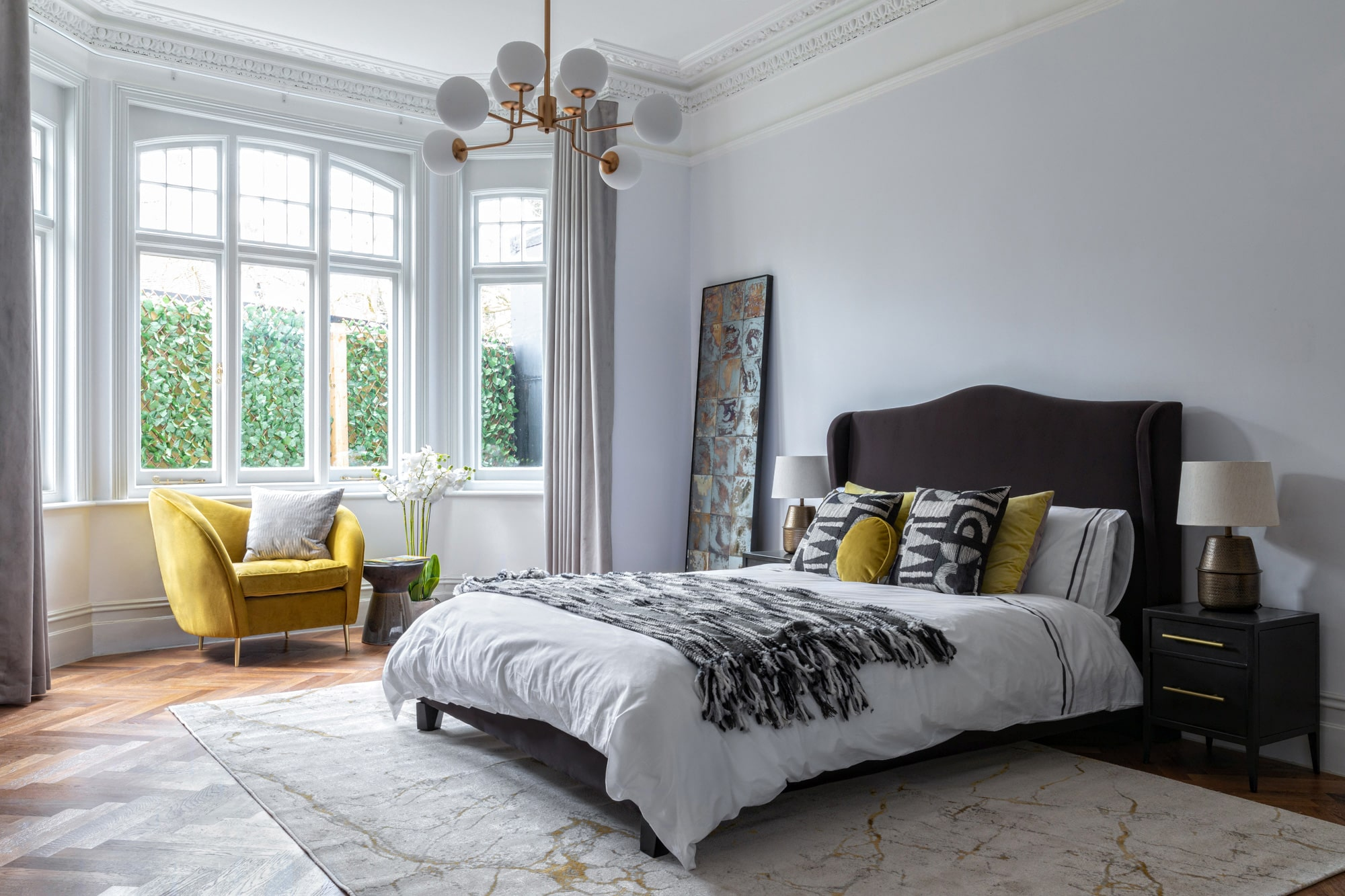 Interior photograph of a bedroom with light blue walls, brown velvet bed, yellow armchair and beautiful ceiling lighting