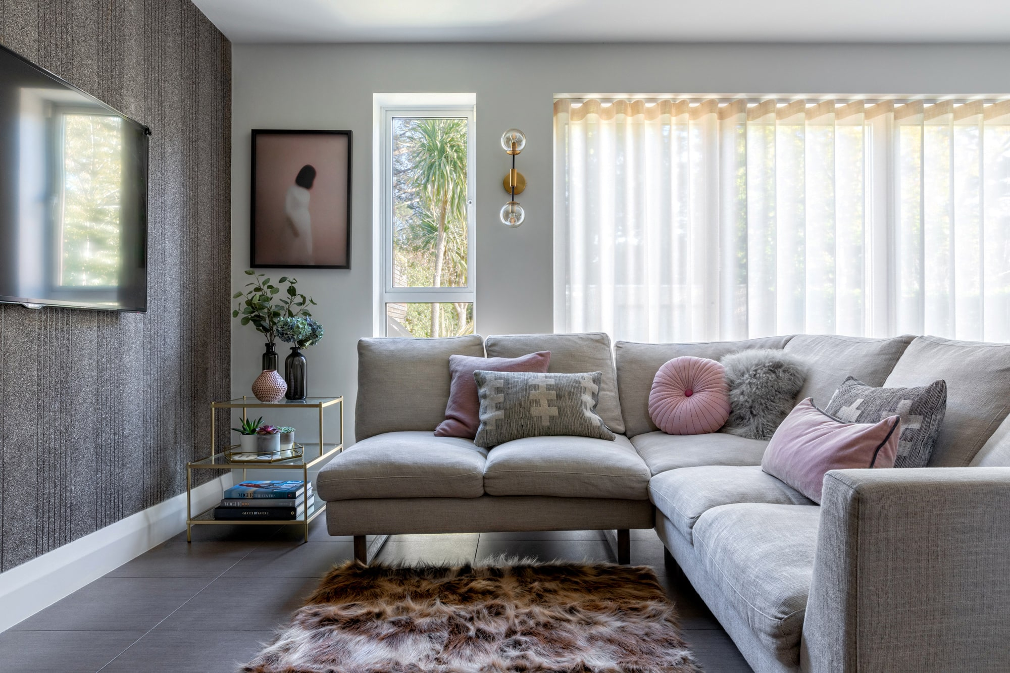 interior photo of a living room: grey feature wall, light grey sofa with pink and grey cushions; glass side table, girl on pink background art