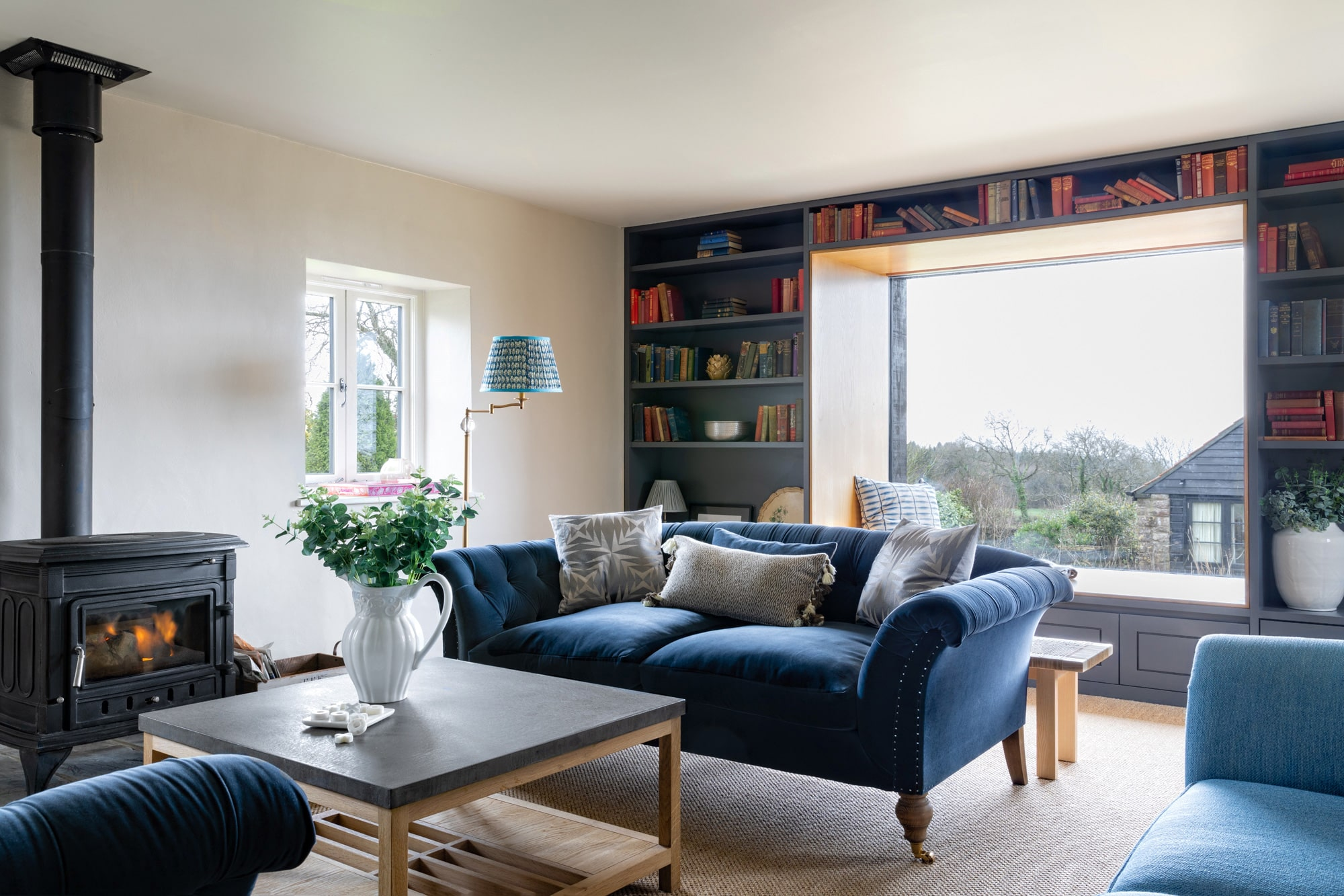 interior photo of a sitting room: 2 velvet dark blue sofas; square coffee table with a vase on it; a huge window with a reading nook; shelves with books