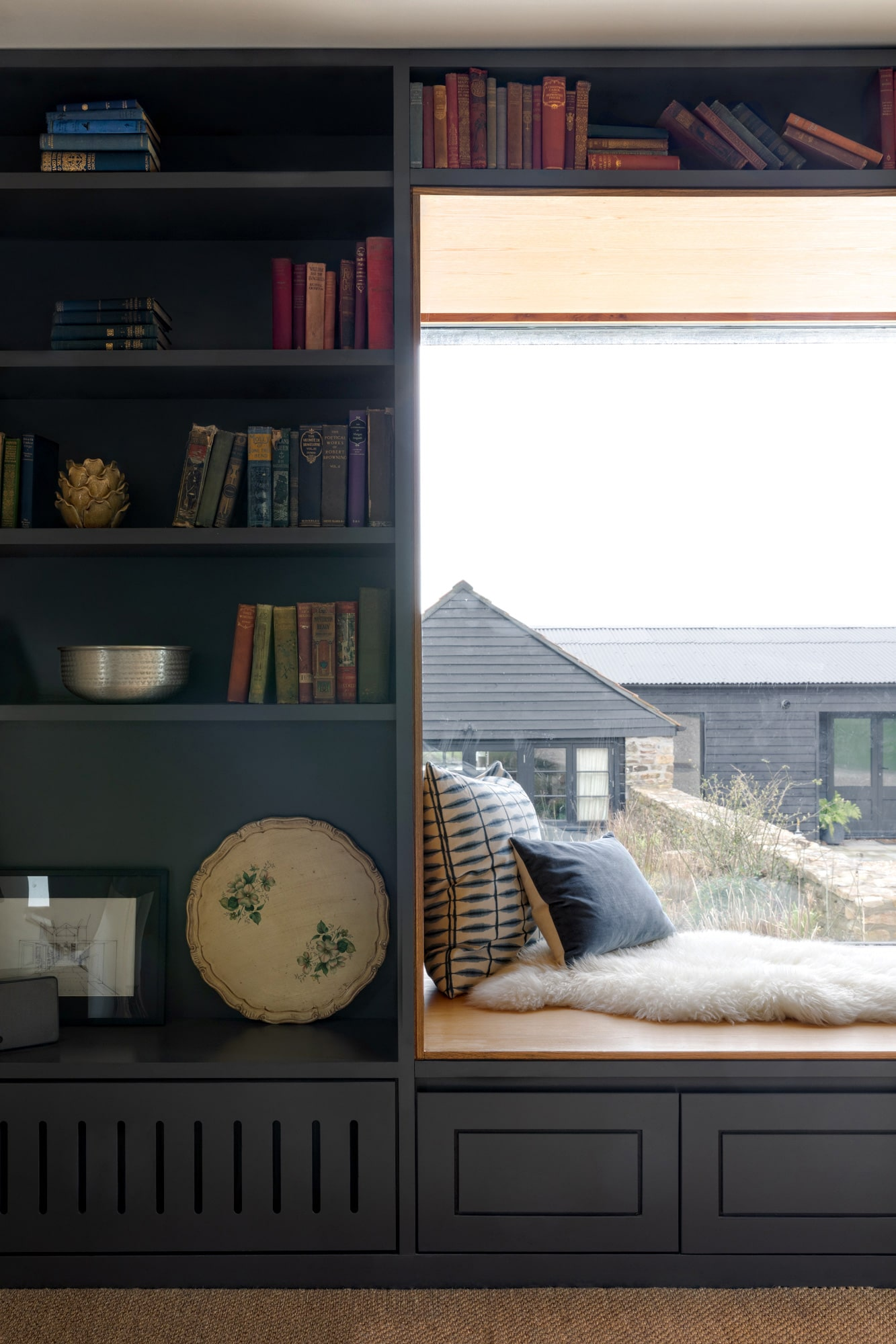 interior detail photo of a sitting room: a reading nook next to the window with 2 cushions; shelving unit with book on the left side of the window