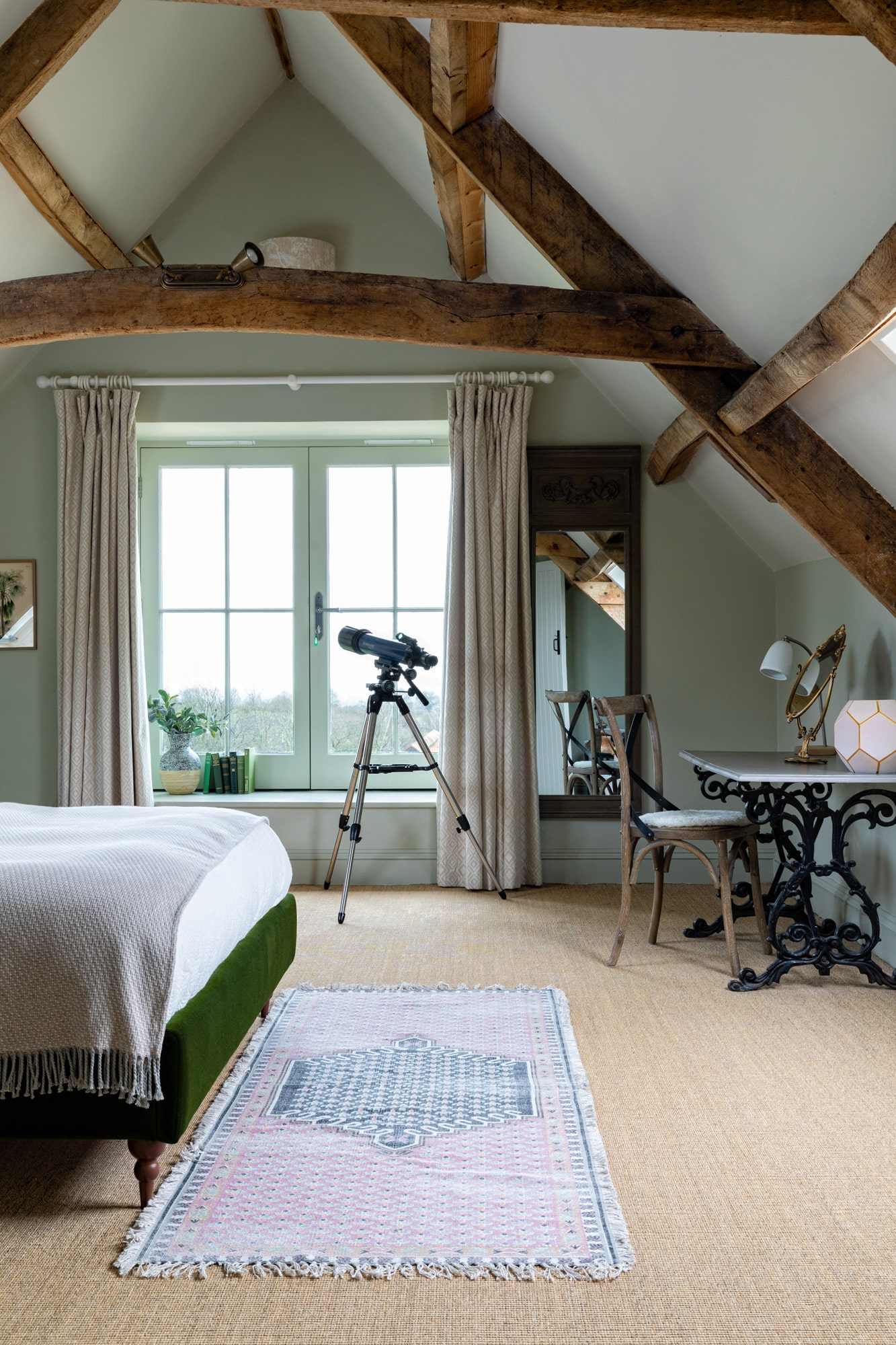Interior photo of a barn bedroom: olive green walls; telescope, edge of the bed; a desk with lamp and chair