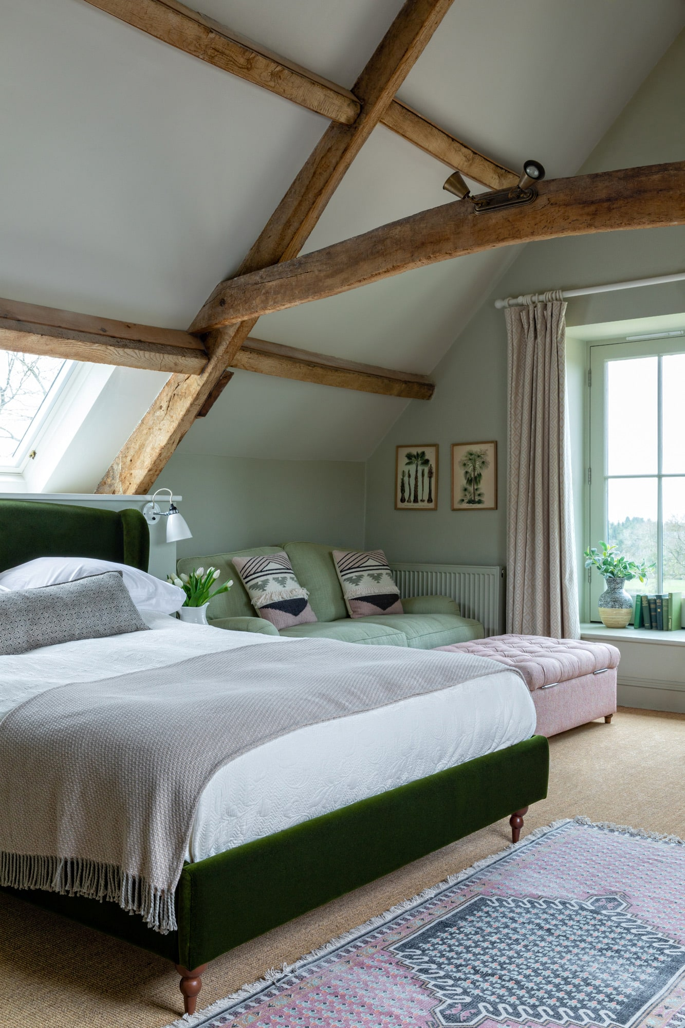 renovated barn bedroom: olive green walls; dark green velvet bed with white linen; bedside table with a vase of tulips; light green sofa and pink soft stool