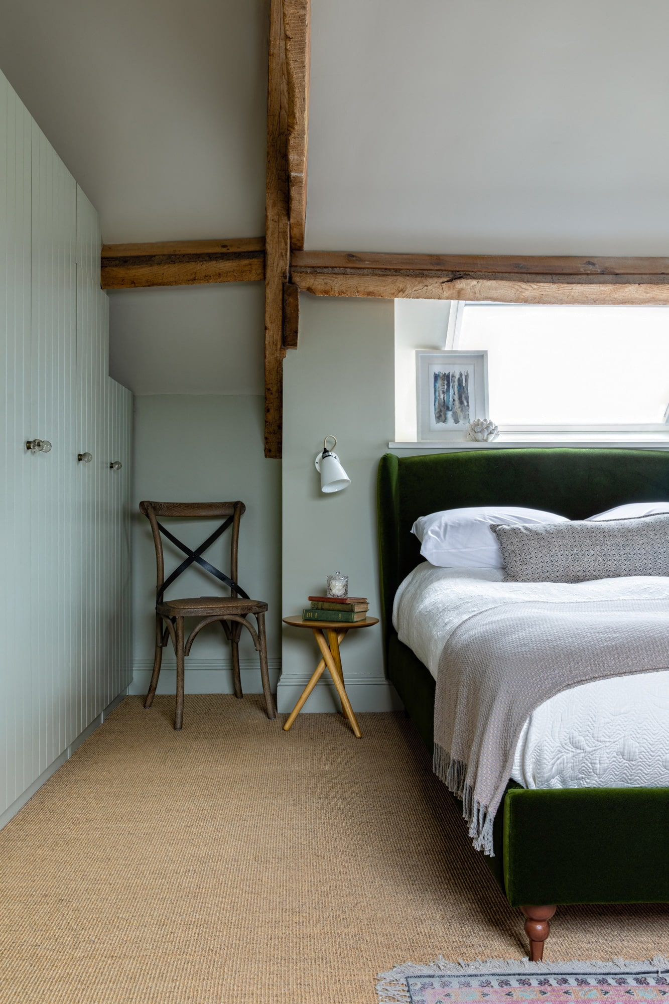 bedroom in a renovated barn; dark green velvet bed with white linen; bedside table; olive green walls and olive green built-in wardrobe