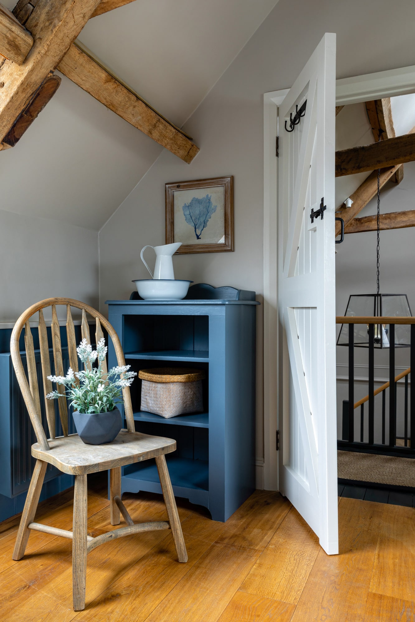 bathroom detail shot: open white door; a chair with a flower pot on it, blue shelving unit by the door