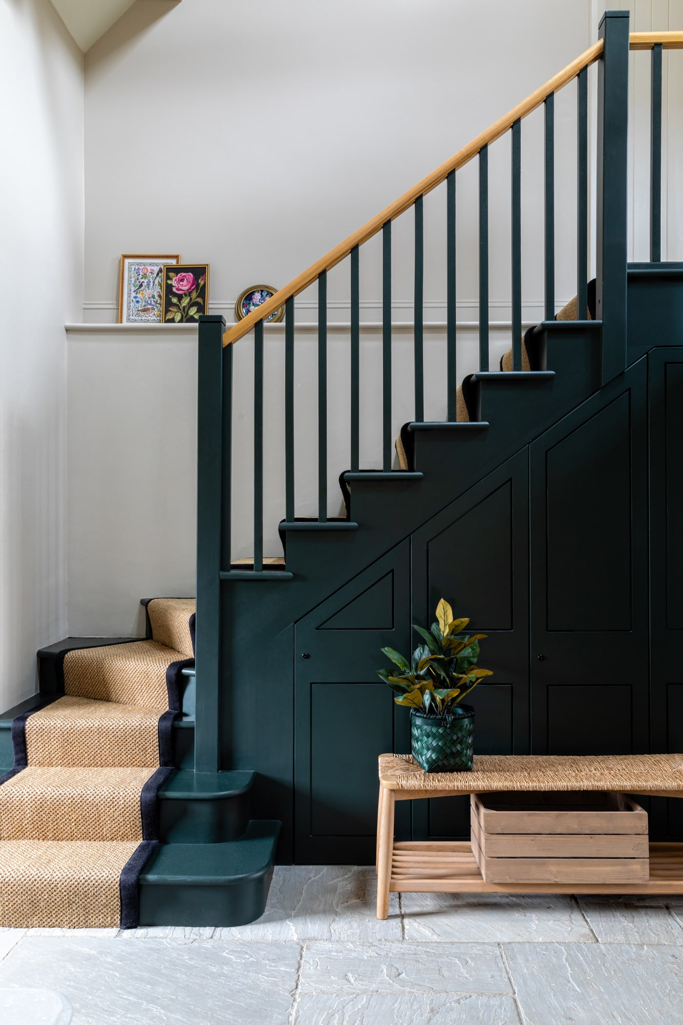 interior photo: dark green staircase with a rattan ranner