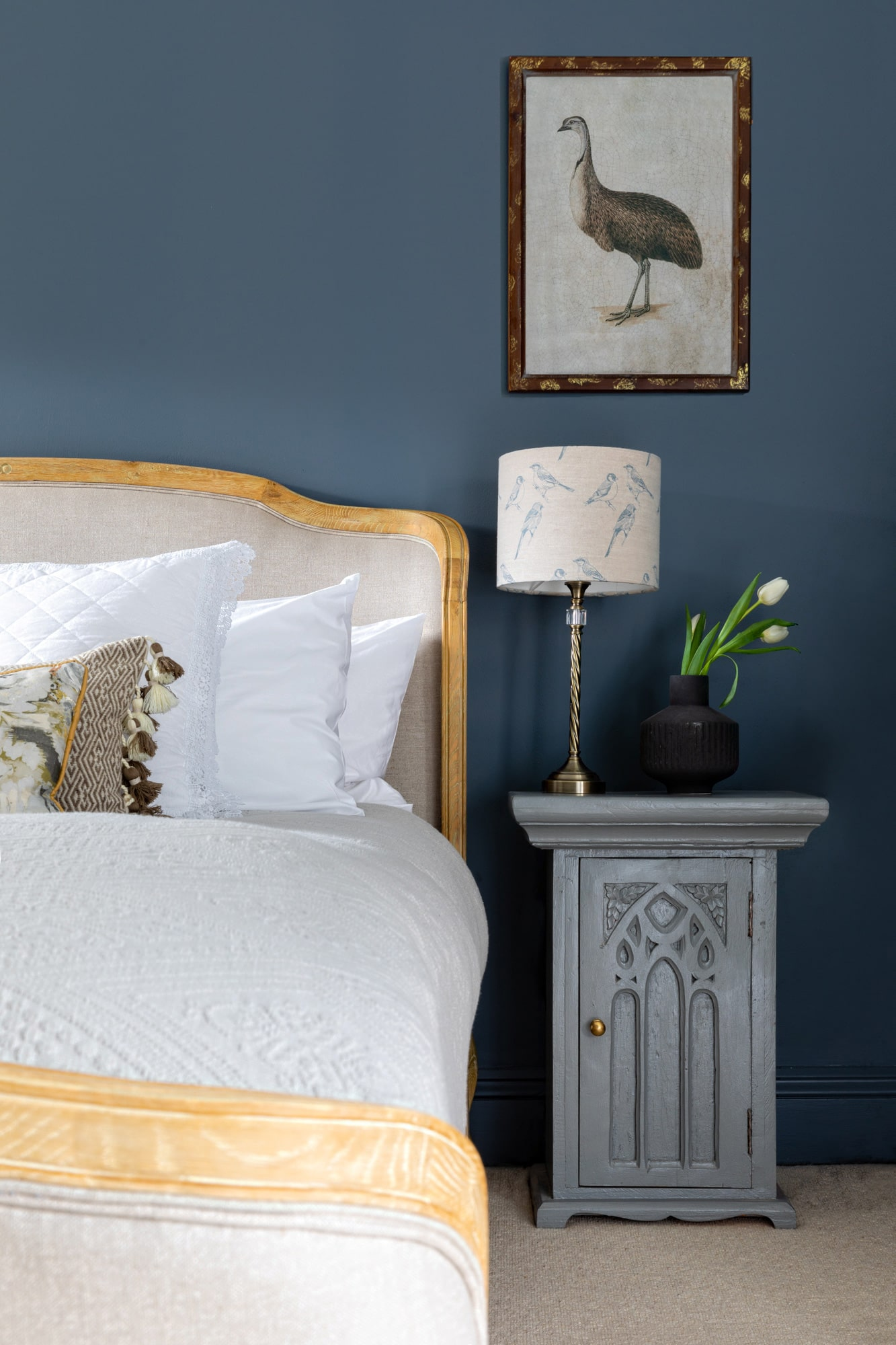 interior detail bedroom photo: dark blue grey walls; bed with white bedding; grey wooden bedside table, lamp and vase with tulips; poster with a bird on the wall