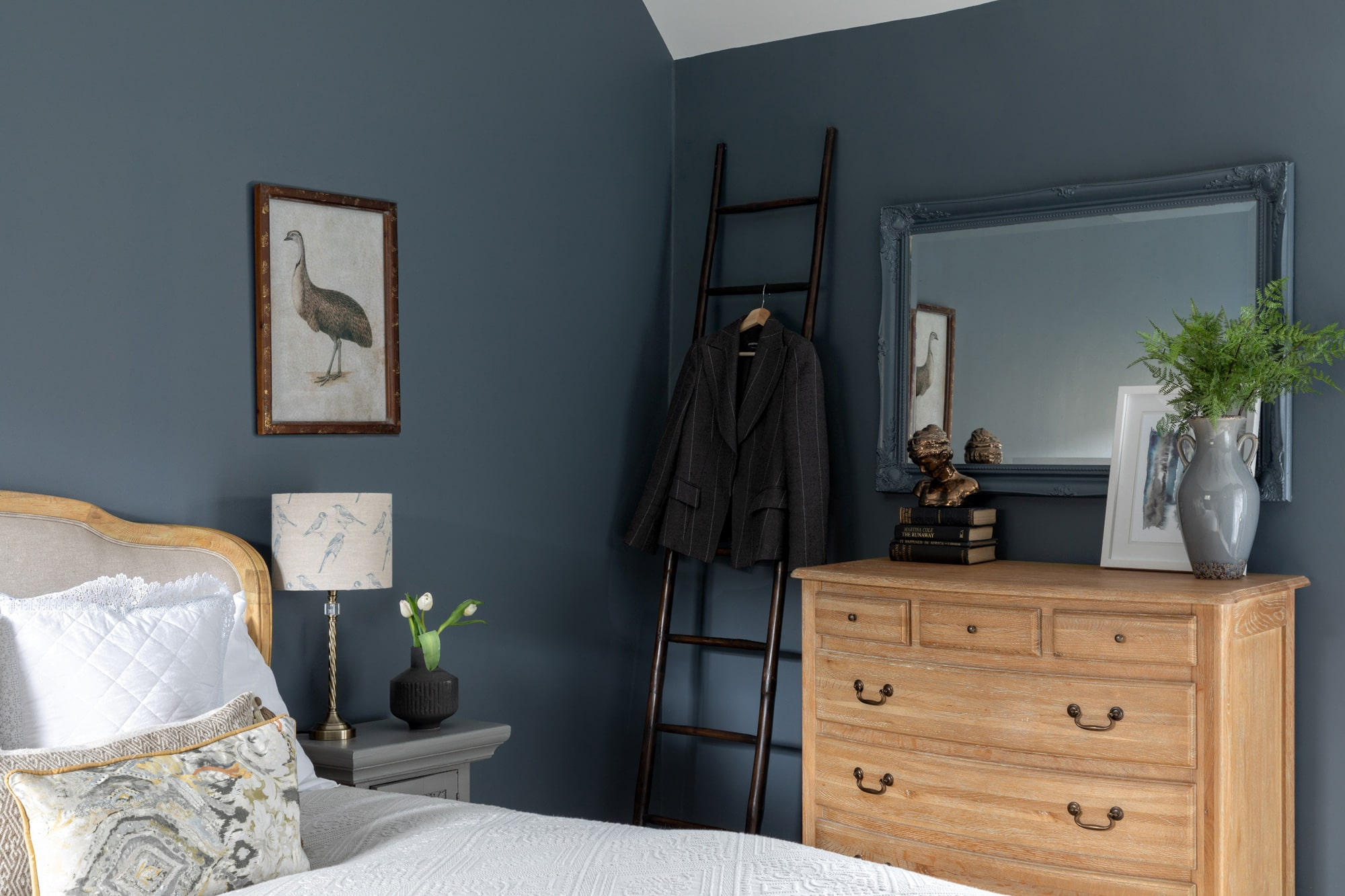 Interior photo of a bedroom: dark grey-blue walls, chest of drawers with a mirror above; white bed linen; grey bedside table; poster art with a bird