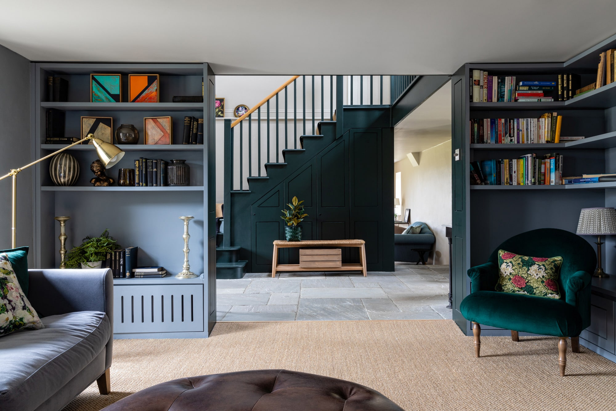 living room photograph: green and blue shelving units with books and accessories; round soft table; room overlooks a dark green straircase