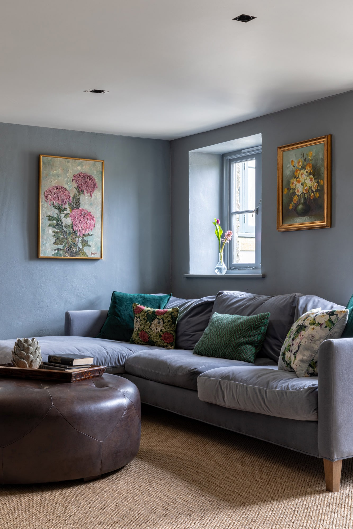 Interior photo of a sitting area: grey velvet sofa with floral and green cushions; two floral art works on the walls