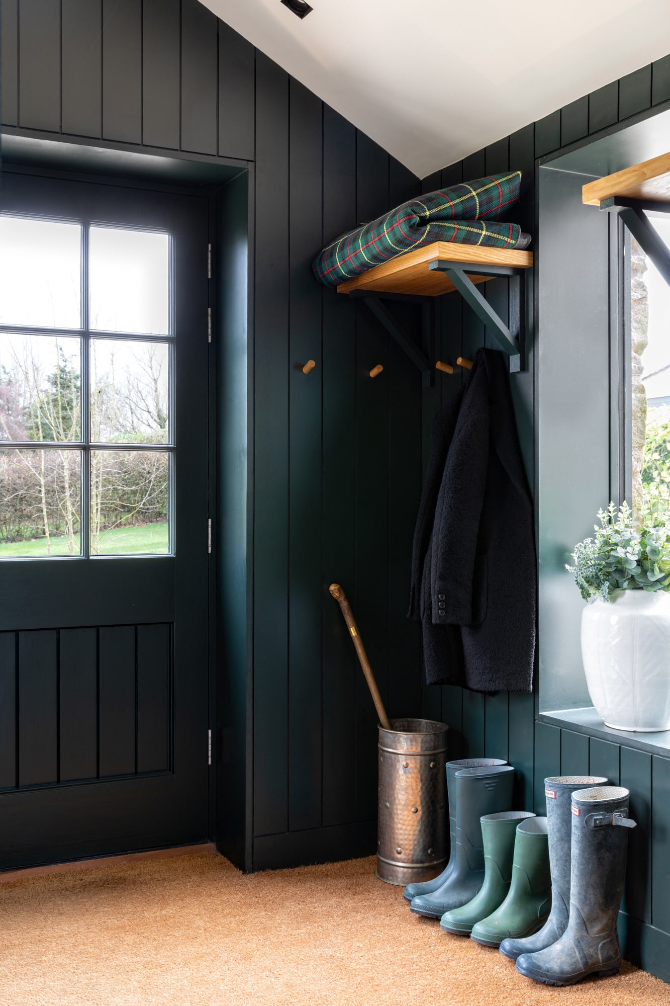 boot room with dark green panels; wellies muddy boots