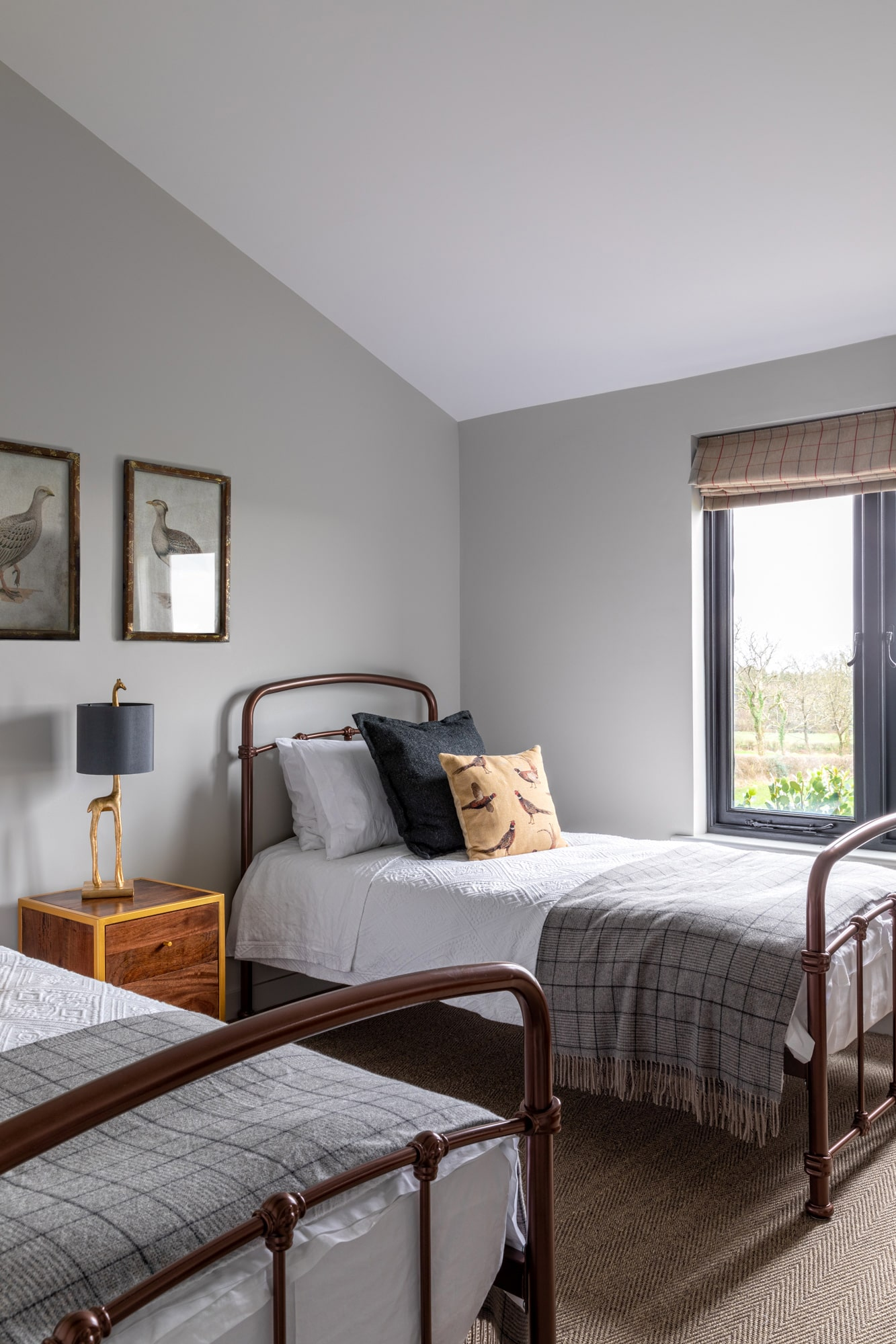Kids' bedroom: grey walls; 2 single beds; brown and gold beside table in between beds with a lamp in a form of giraffe