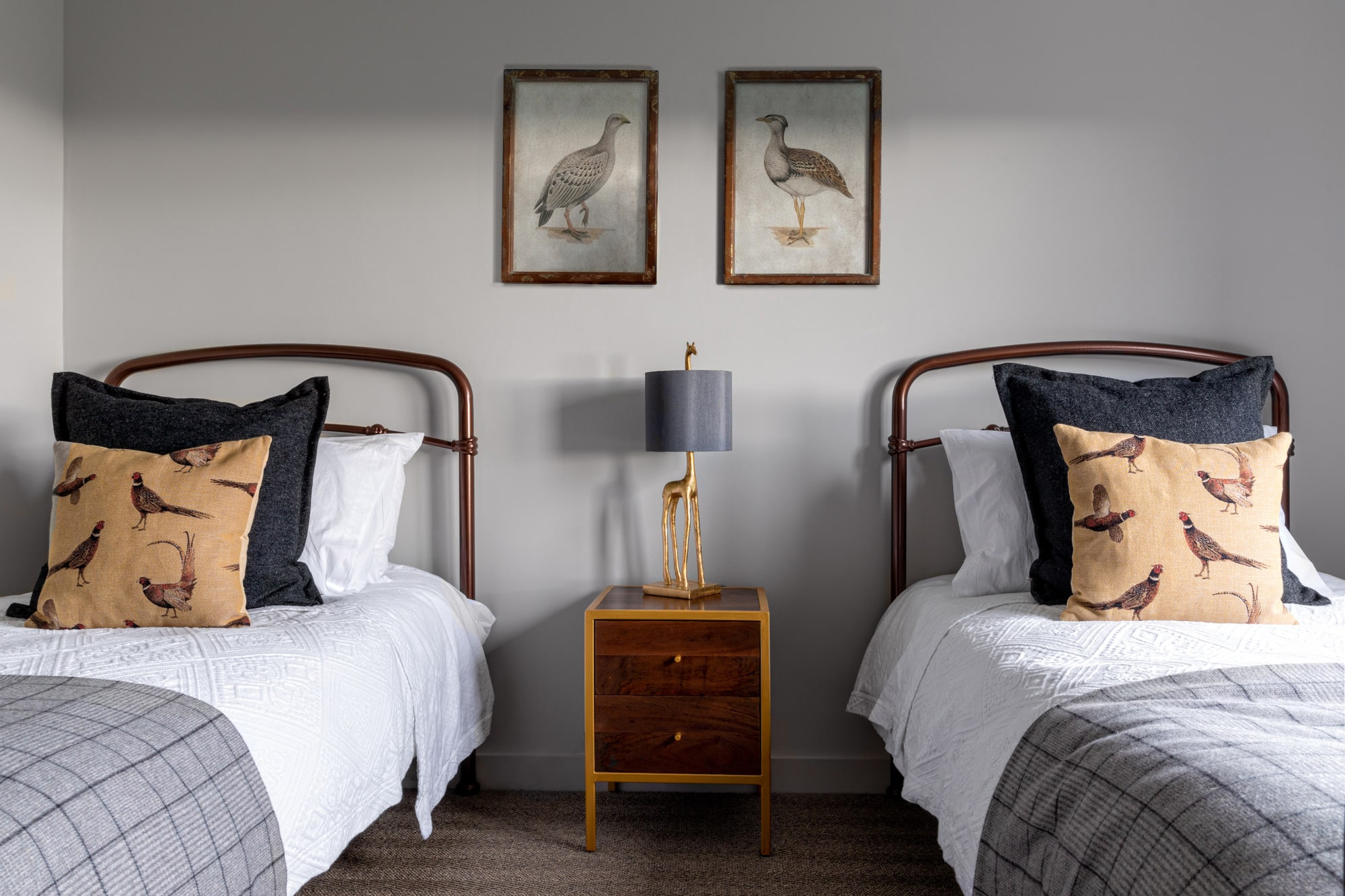 Kids' bedroom: grey walls; 2 single beds; brown and gold beside table in between beds with a lamp in a form of giraffe; two posters with birds on the wall