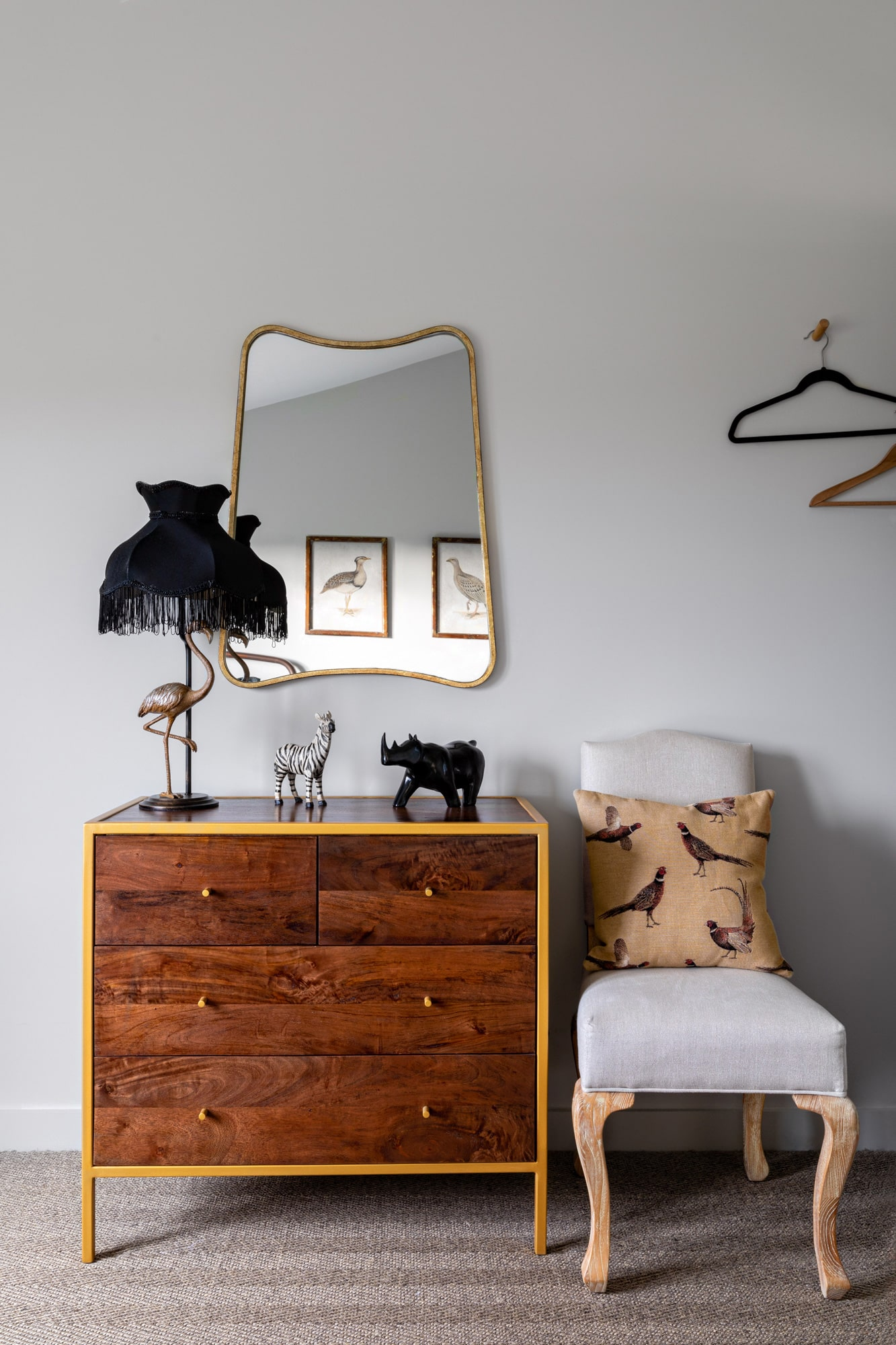 Kids's bedroom detail: brown and gold chest of drawers, a mirror above, black lamp, a grey chair with a cushion; fun figures of animals on the chest of drawers