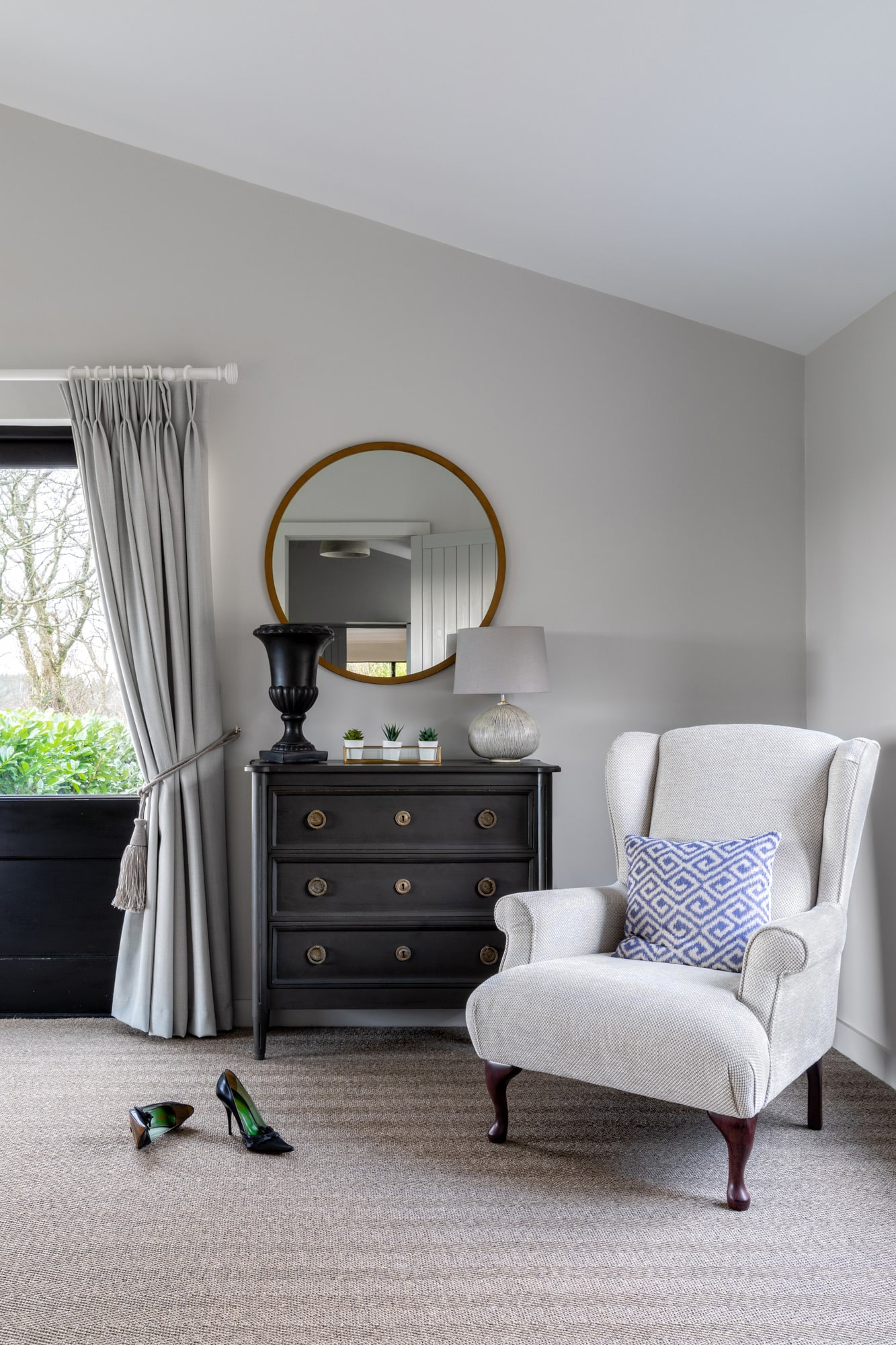 Interior photo of a bedroom: dark chest of drawers, llight beige armchair, round mirror above the chest of drawers and a glass door to a garden