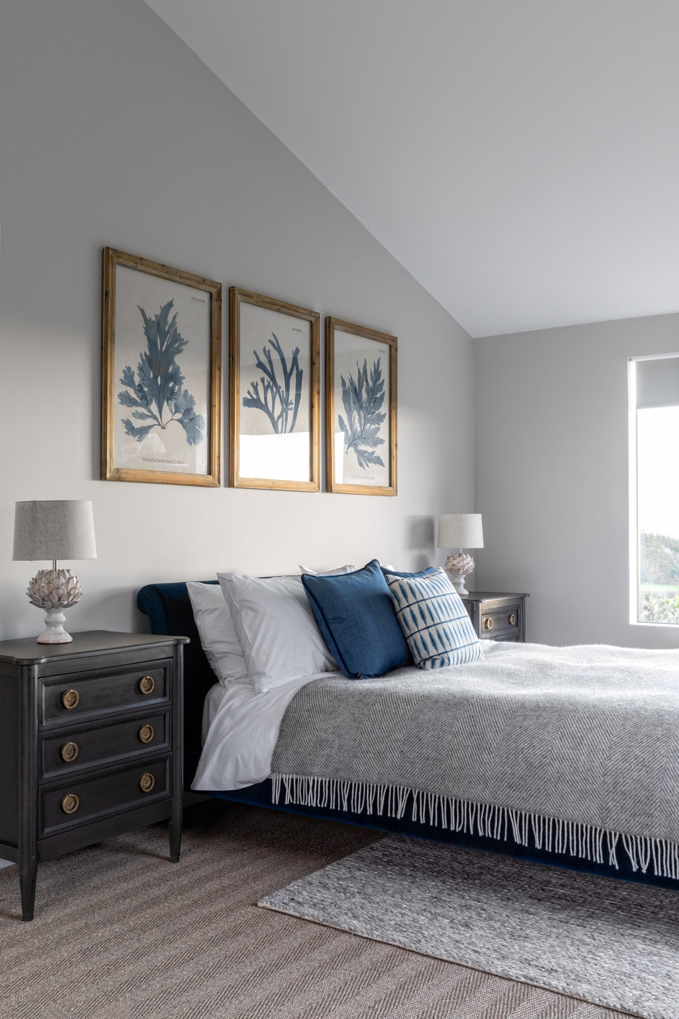 Interior photo of a bedroom, grey walls, a bed with 2 bedside tables, 3 posters above the bed.