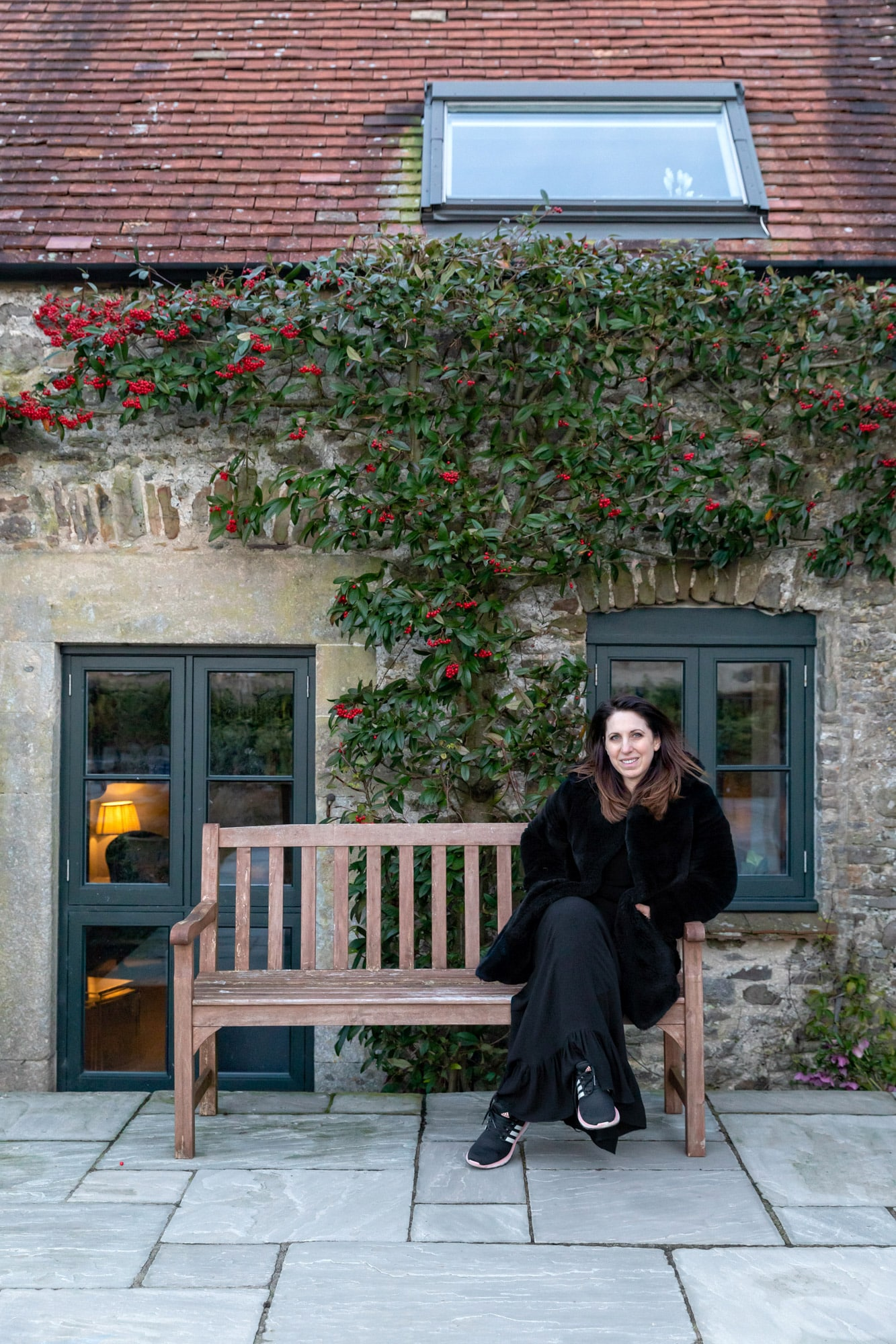 portrait of an interior designer sitting on the bench in front of the barn she decorated