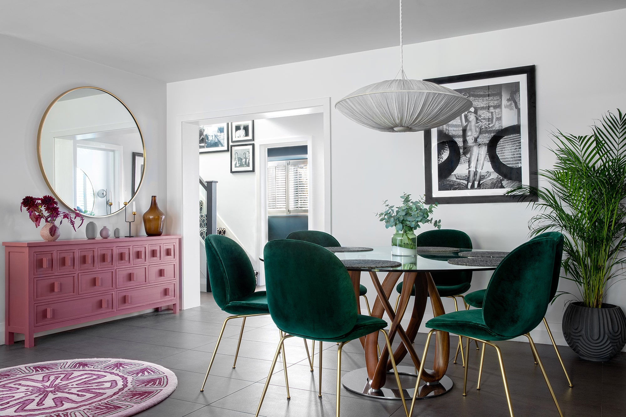 Interior design photo: living room with pink cabinet and round mirror; round table with a glass top, green velvet chairs; black and white photo of a woman on the wall