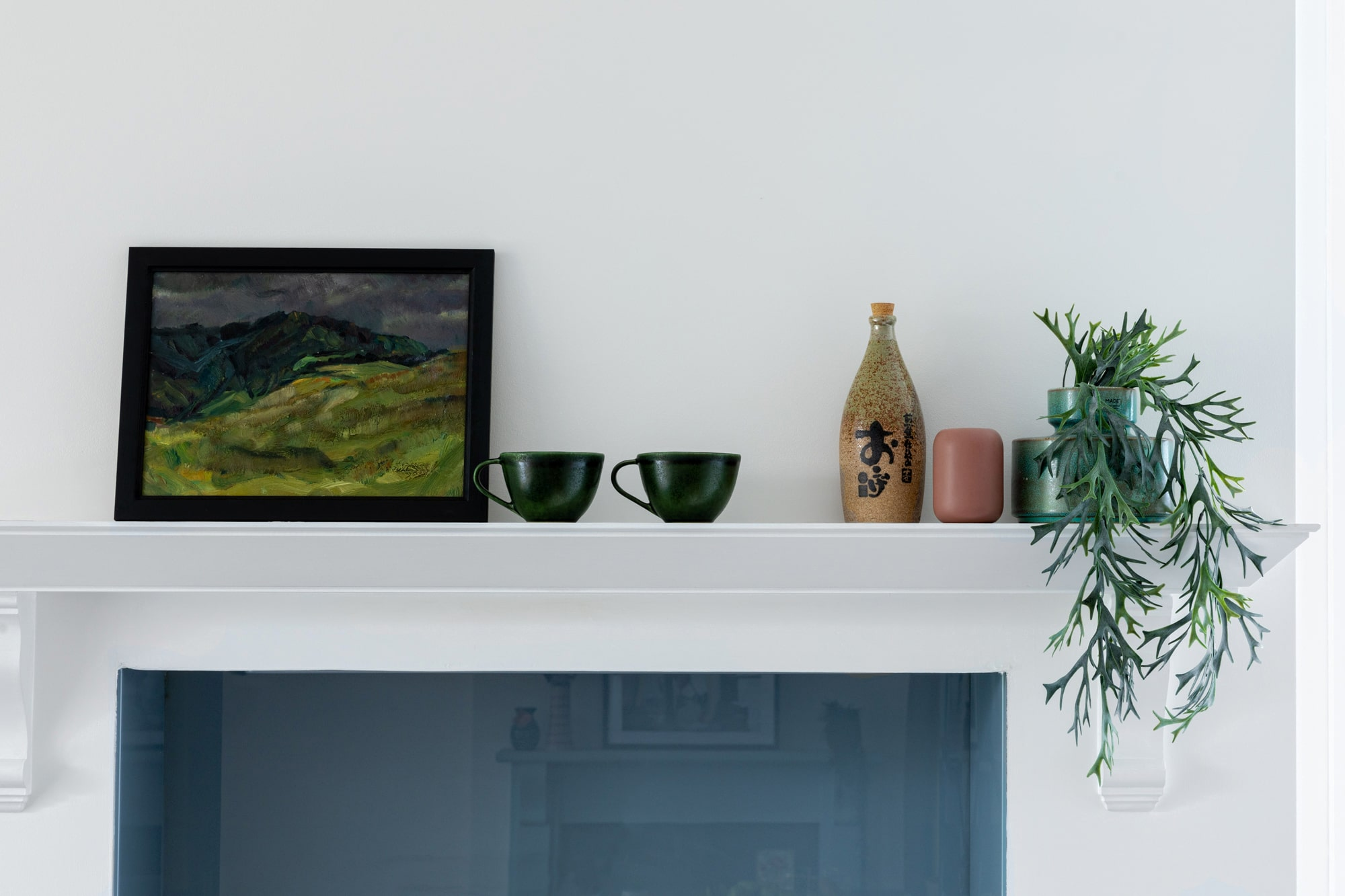 Interior detail photo: kitchen shelf with 2 dark green mugs, a painting, plant in  vase and other accessories